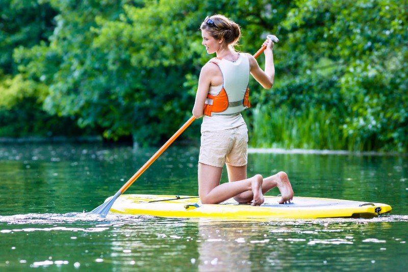 bigstock-Woman-paddling-with-surfboard-70675171